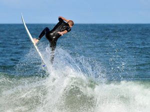 professional surfer jumping off wave